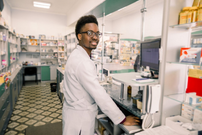 pharmacist working with computer behind counter in pharmacy